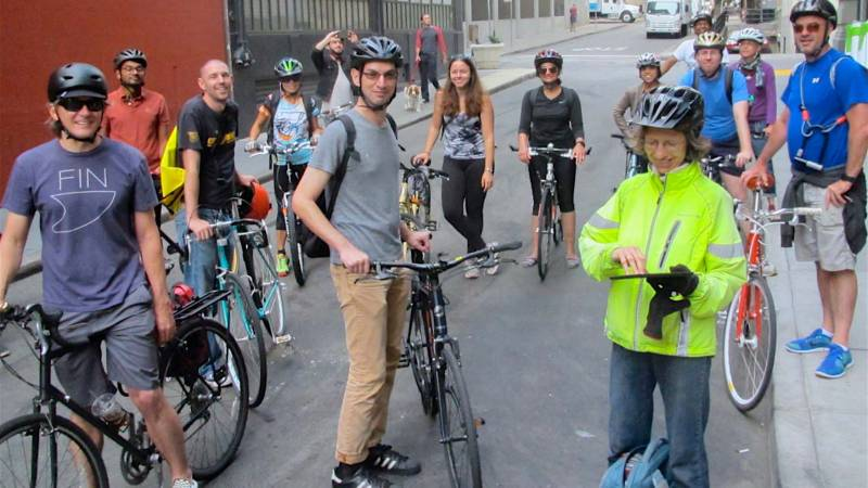 Many cyclists posing for a photo in the middle of a guided tour.