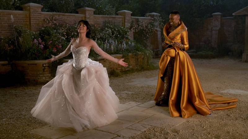 Cinderella, in a white tulle dress stands with arms outstretched as Fab G, wearing a gold formal gown, proudly watches on, smiling.