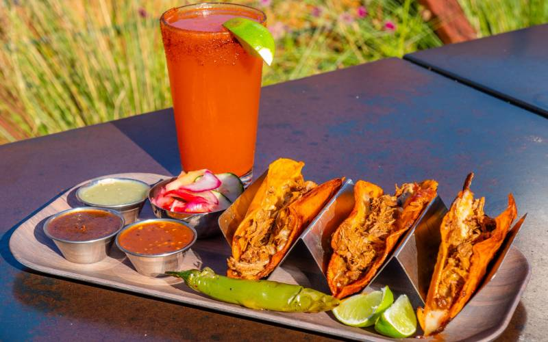 A michelada and a tray of three quesabirria tacos on an outdoor table.