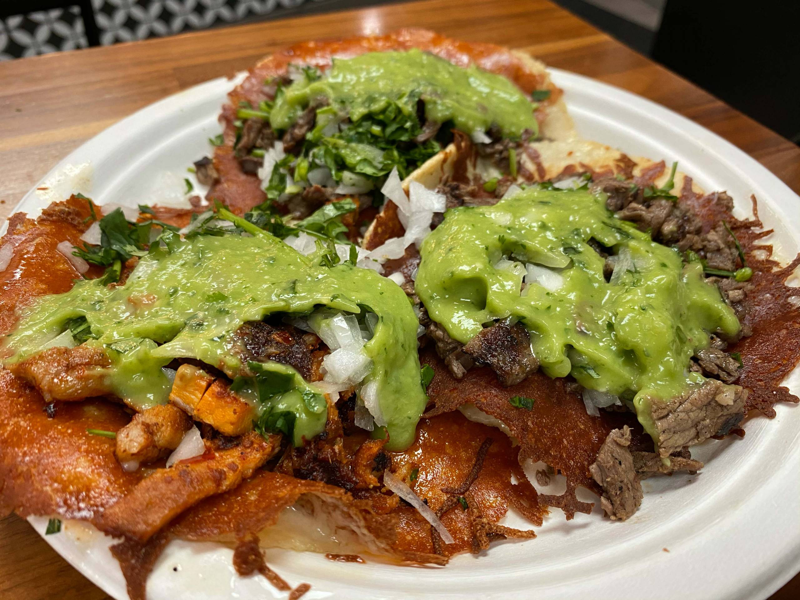 Three tacos, topped with guacamole and crispy cheese, on a paper plate.