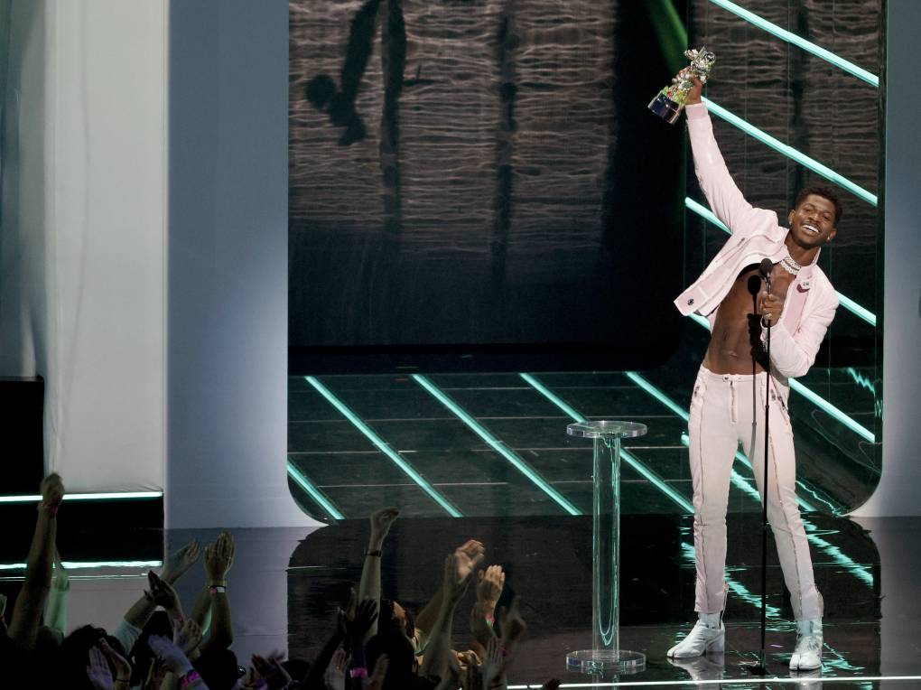 Little Nas X wearing white pants, white jacket and no shirt, smiles broadly and waves an award over his head.