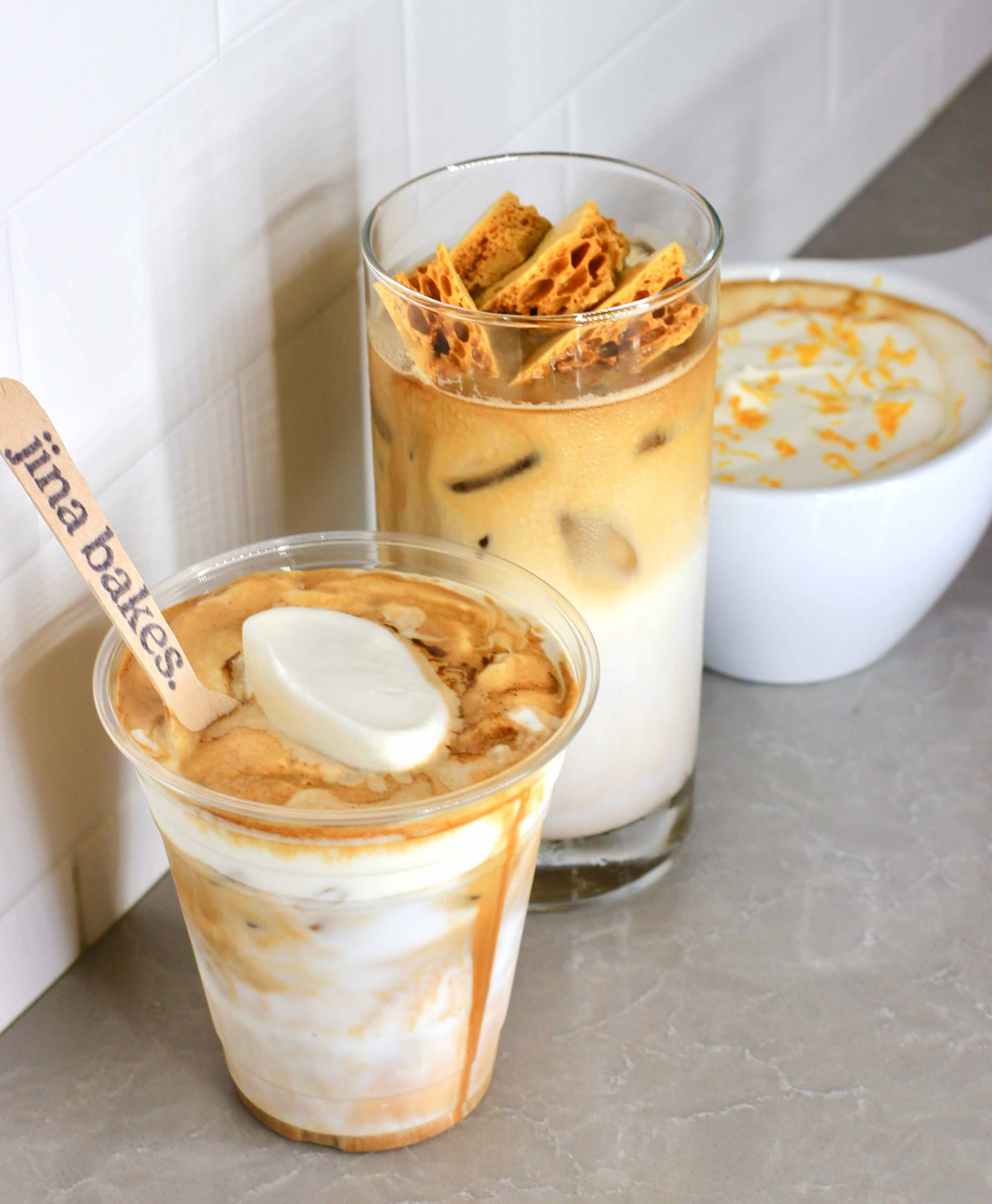 Three coffee drinks on a countertop, variously topped with whipped cream and honeycomb toffee candy.