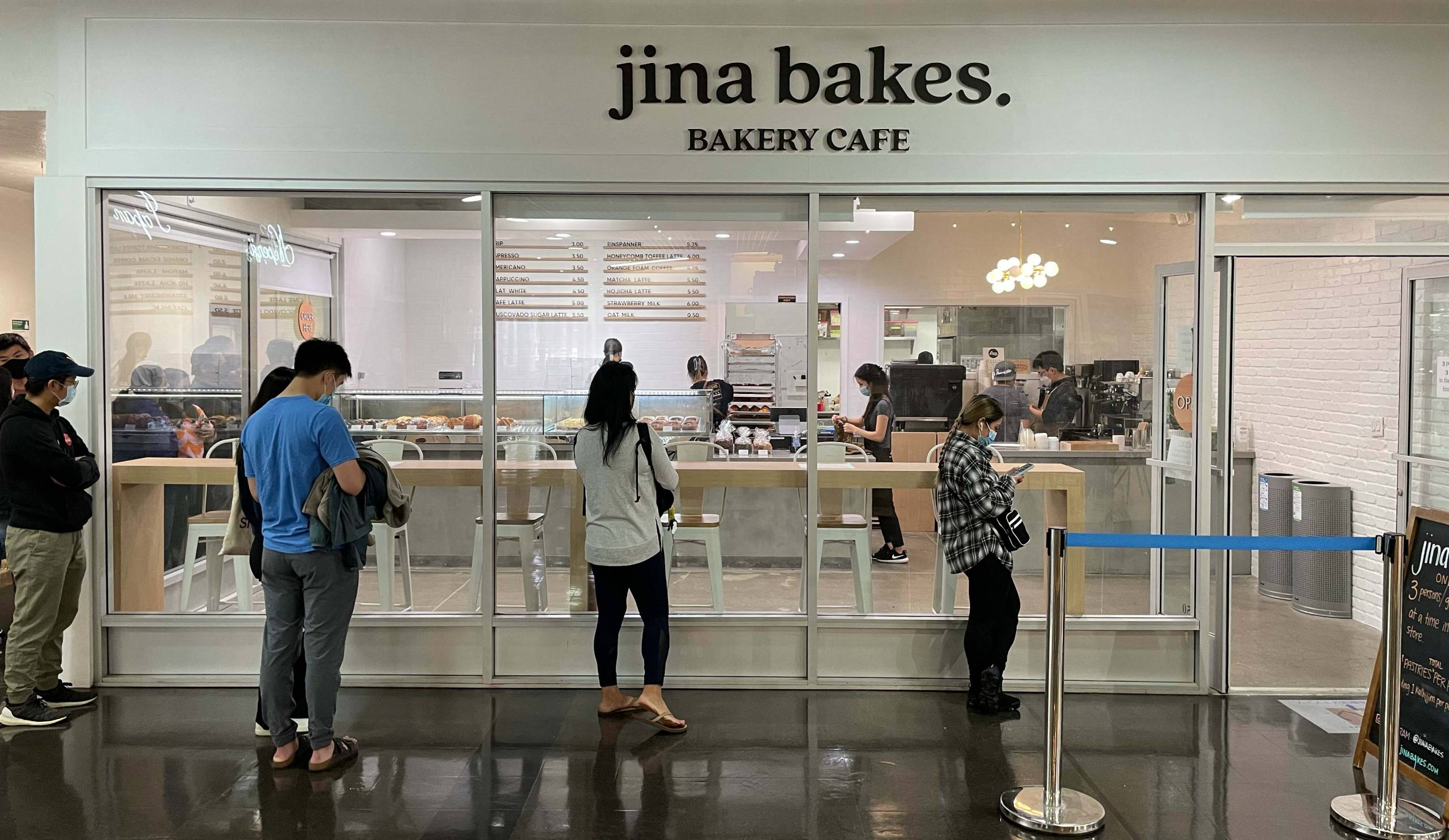 """A line of customers waits outside of a bakery; the sign above reads """"jina bakes."""""""