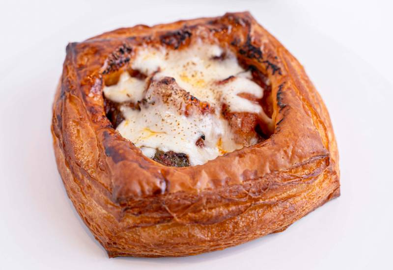A square croissant topped with meat and charred, melted cheese.