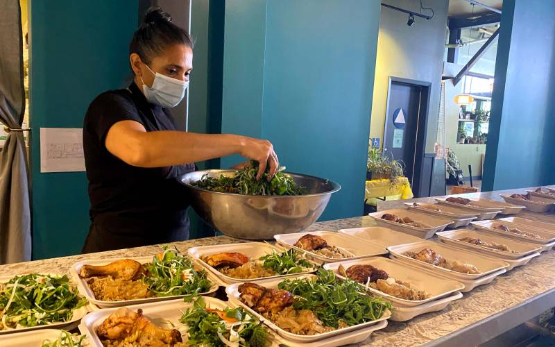 A woman wearing a face mask transfers portions of salad greens into takeout containers lined up on the counter.