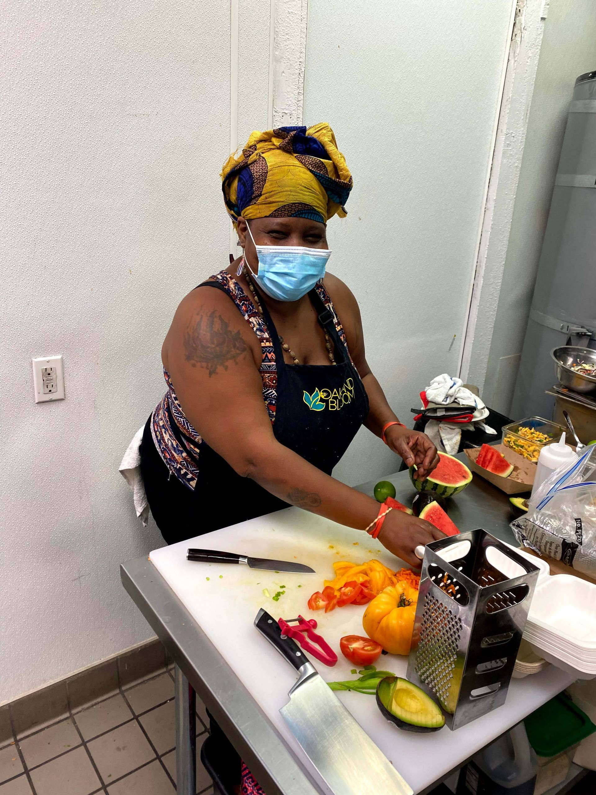 A Black woman wearing a face mask and black apron cuts up orange and red peppers on a small kitchen prep counter.