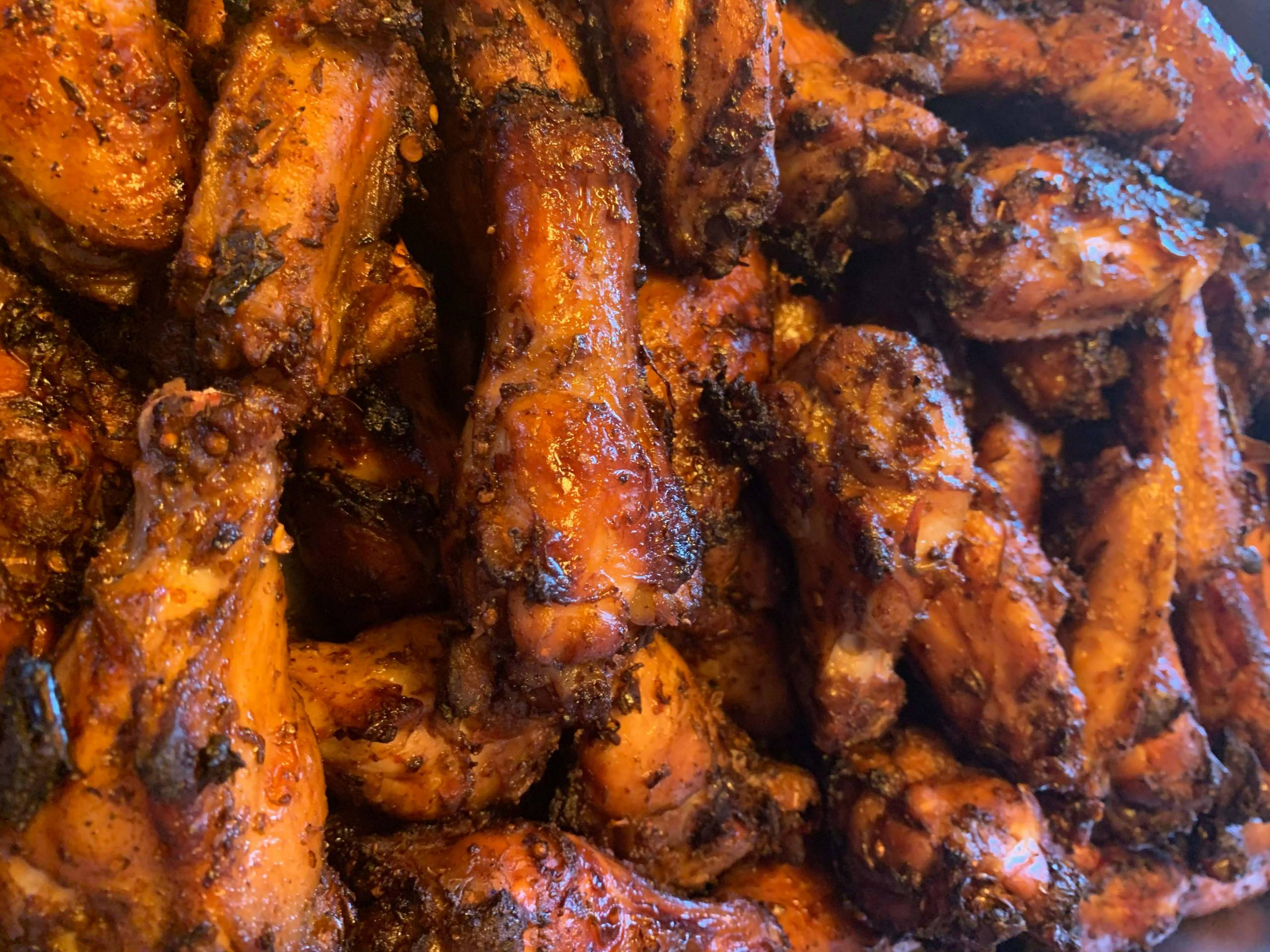 Close-up of a tray of red, spice-stained chicken wings with a hint of charring.