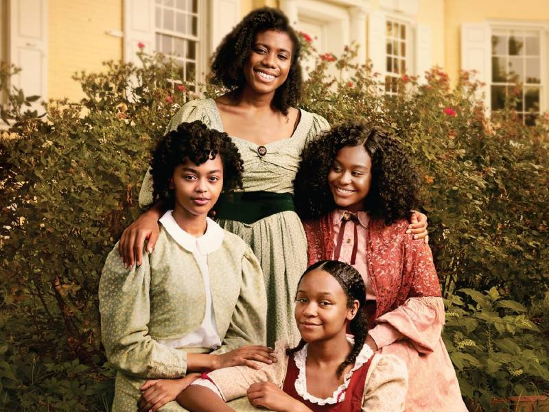 Four Black women pose together, smiling, in colorful 1860s period dresses, in a garden.