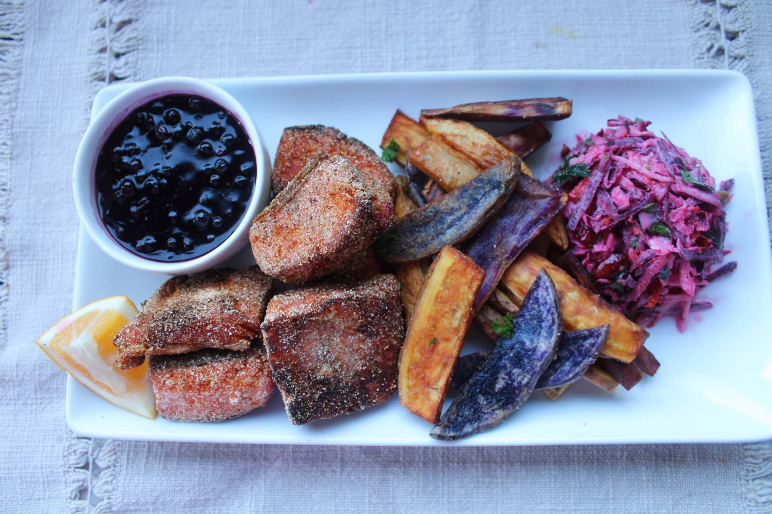 A plate of fried salmon and sweet potato fries, with berry sauce for dipping.
