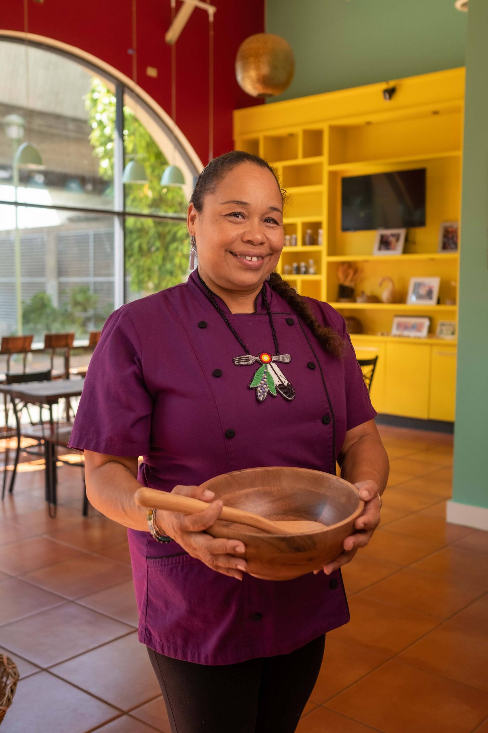 A chef holds a wooden bowl inside her restaurant.