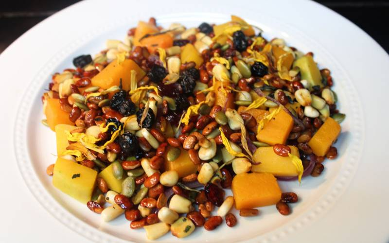 A colorful salad featuring corn, beans and squash on a white plate.