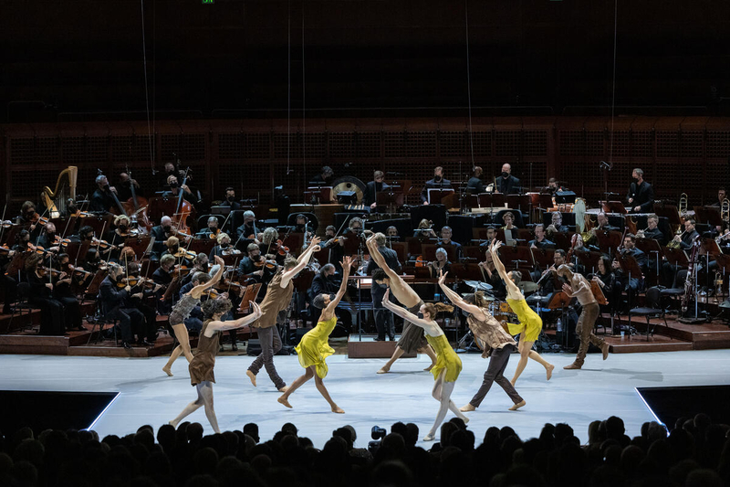 Male and female ballet dancers gather in a symmetrical formation in front of an orchestra.