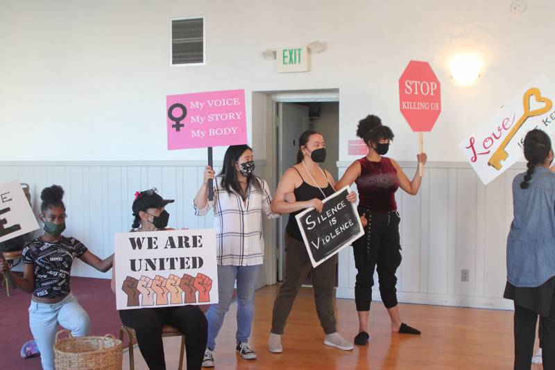 Singers in rehearsal hold protest signs.