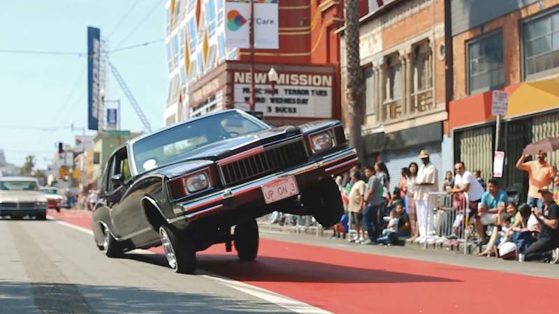 A lowrider rides on three wheels in the Mission District in 2016.