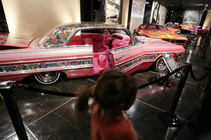 Visitors to the Peterson Automobile Museum in Los Angeles examine the Gypsy Rose, a 1964 Chevrolet Impala and one of the most famous lowriders in history, in this 2008 file photo.