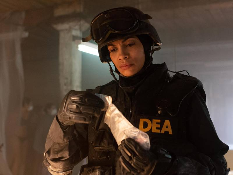 A woman wearing a SWAT uniform and helmet, as well as a vest marked DEA, frowns as she examines a plastic bag containing pills.