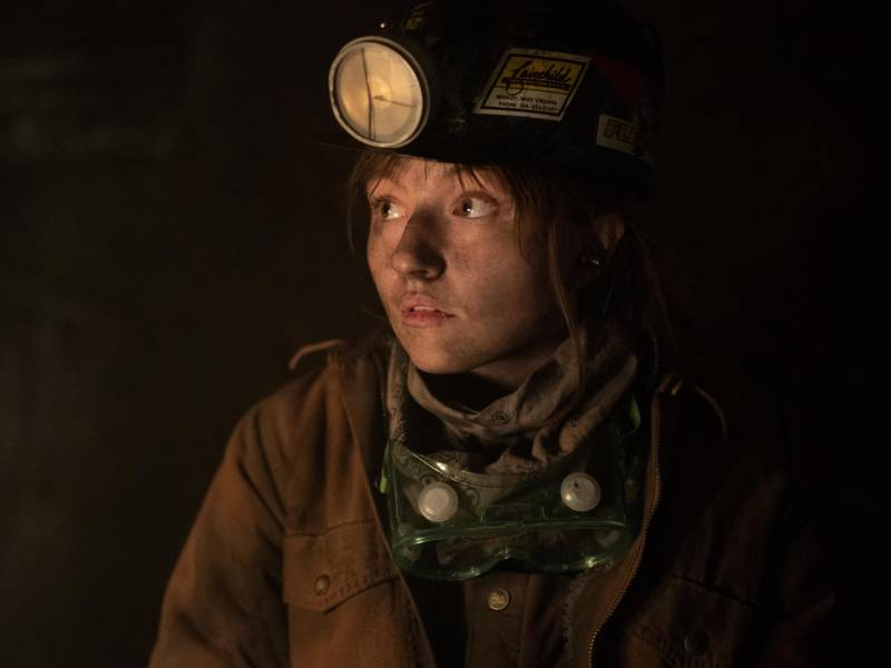 A young woman wearing a miner's helmet, her face smudged with coal, glances cautiously to her right.