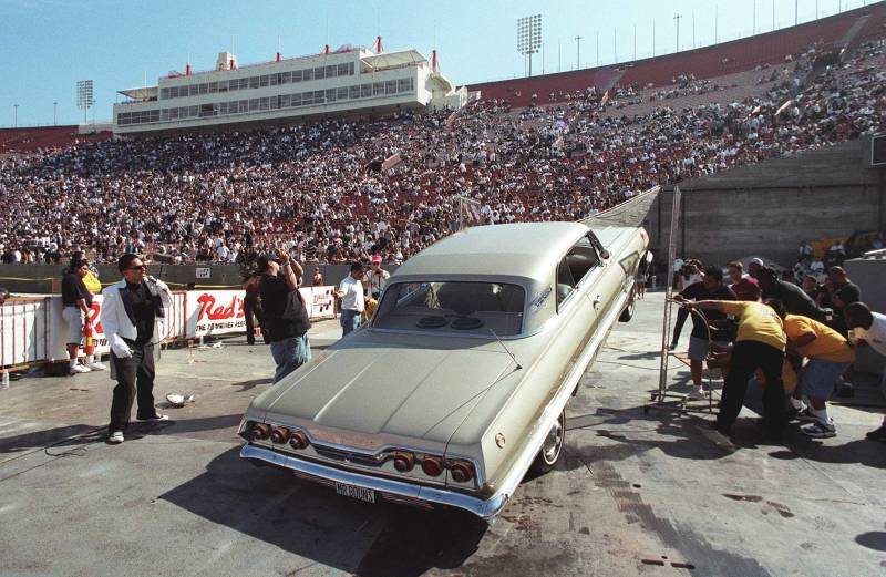 Lowriders bounce as high as possible during a car hopping contest at the Los Angeles Coliseum in 1996.