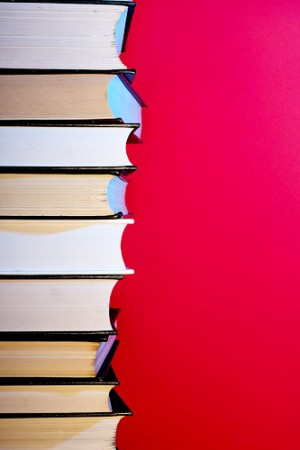 Stack of hardcover encyclopedias against red background