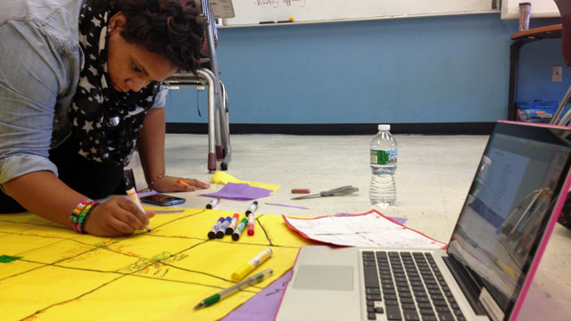 A Science Leadership Academy sophomore puts the finishing touches on a geometry project during her lunch period.