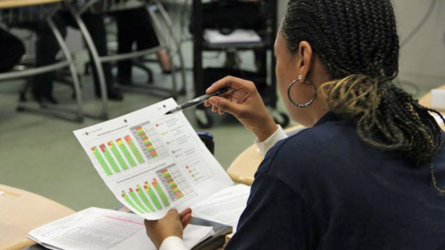A seventh grade teacher at Clinton Middle School in Los Angeles looks at Early Warning Indicator data during a morning meeting. (Alyson Bryant/Youth Radio)