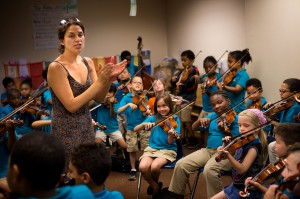 Kathleen Jara, co-director of the El Sistema program at the Conservatory Lab Charter School in Boston, directs orchestra students during a rehearsal for their year-end recital. (Jesse Costa/WBUR)