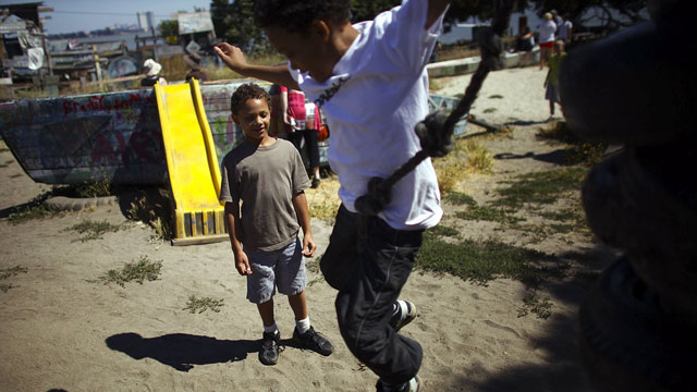 Deion Jefferson, 10, and Samuel Jefferson, 7, take turns climbing and jumping off a stack of old tires at the Berkeley Adventure Playground. David Gilkey/NPR)
