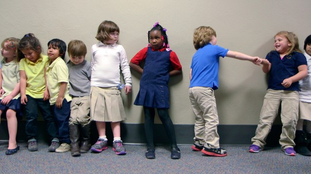 Preschool students from Nikki Jones' class at Porter Early Childhood Development Center in Tulsa line up in the hallway on their way back from outside play. (John W. Poole/NPR)