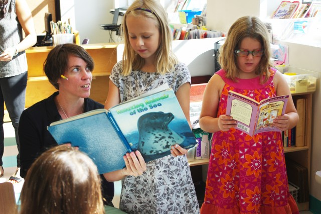 Second-grade teacher Amanda Siepiola reads with Cornelia Blixt and Isabelle Posner-Brown. (Gabrielle Emanuel/NPR)