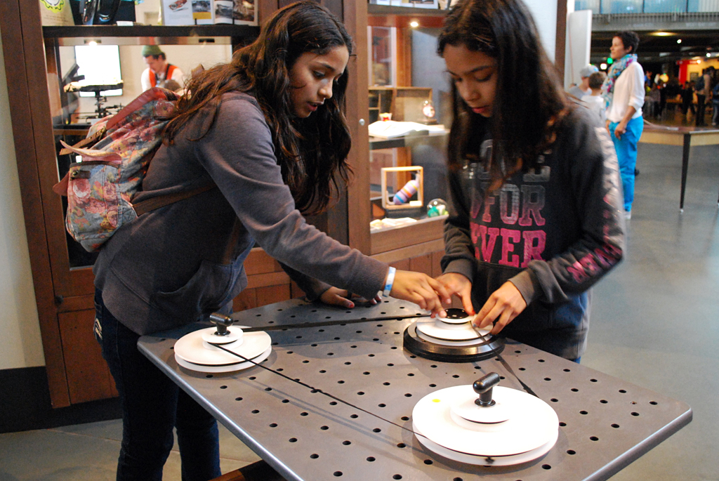 Brenda Hernandez and Marianna Cruz, both sixth-graders from Franklin Middle School in Vallejo, Calif., play with an exhibit on pulleys at the Exploratorium in San Francisco.