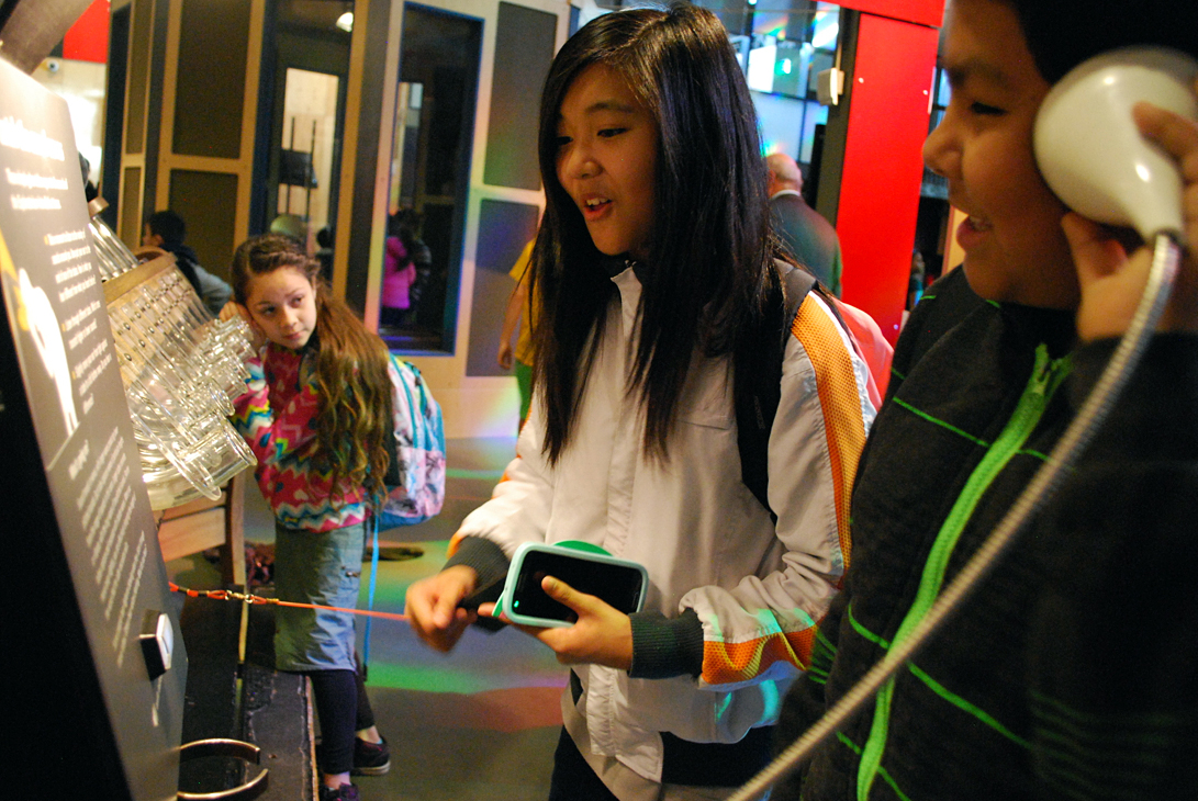 Jasmine Capili and Cesar Viallsenor try to figure out an Exploratorium exhibit on sound waves while their classmate, Stephanie Posadas Torres, listens at the end of a glass tube in the background. All three sixth-grade students are from Vallejo, Calif.