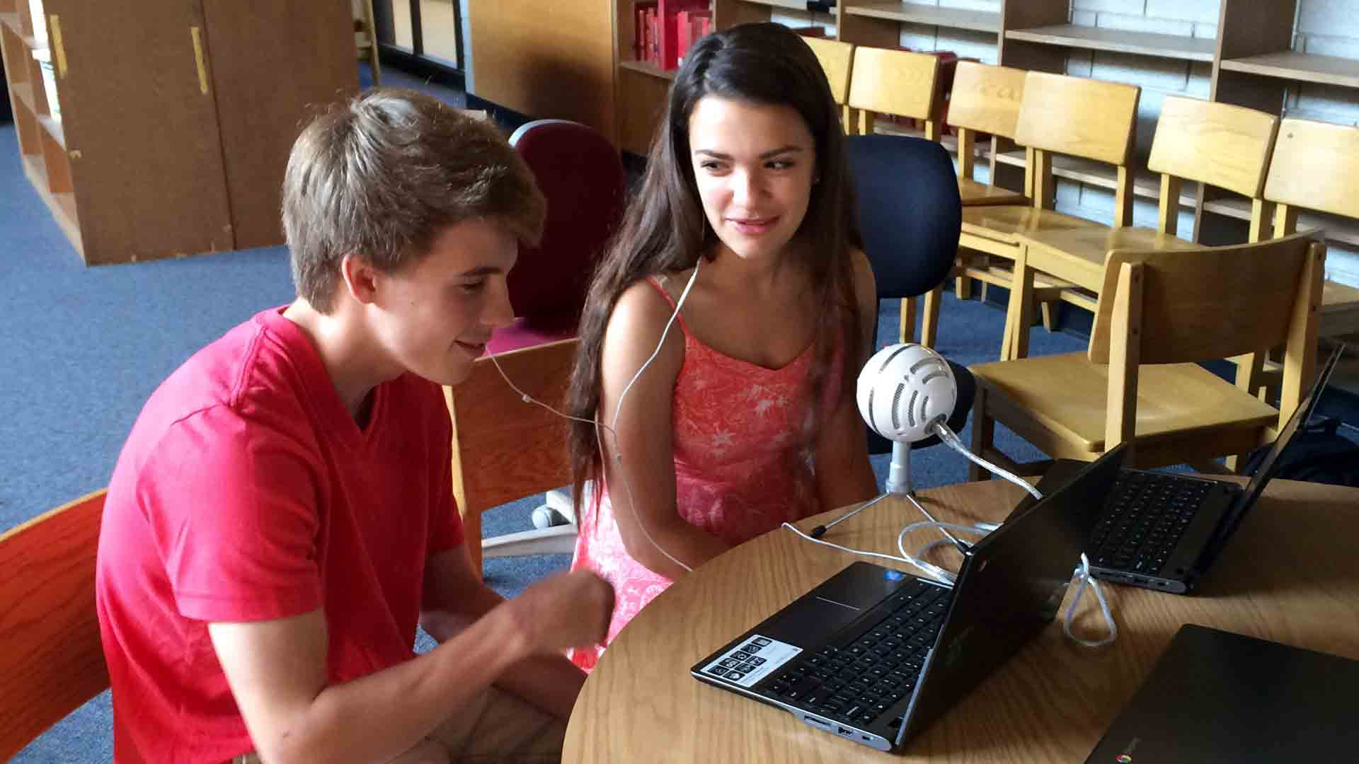 Two students from Norwalk High School record their memoir author's biographical information for their podcast final.