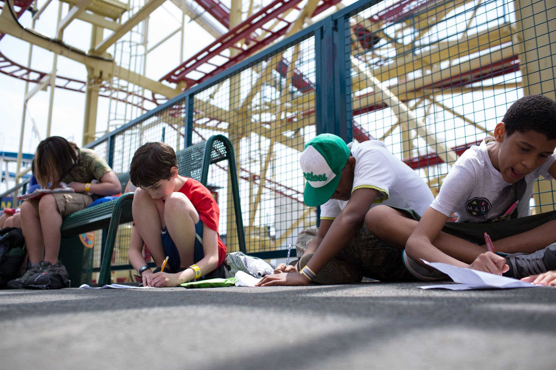 Thea Jones, 12, at left, Etai Kurtzman, 12, Seth Samuel, 12 and Terrell Gantt, 12, fill out game analysis worksheets at Coney Island in Brooklyn, NY May 28, 2015. The group of students from Quest to Learn School took the day trip to Coney Island to analyze user experience on games and rides at Luna Park as part of  their late-spring school curriculum.