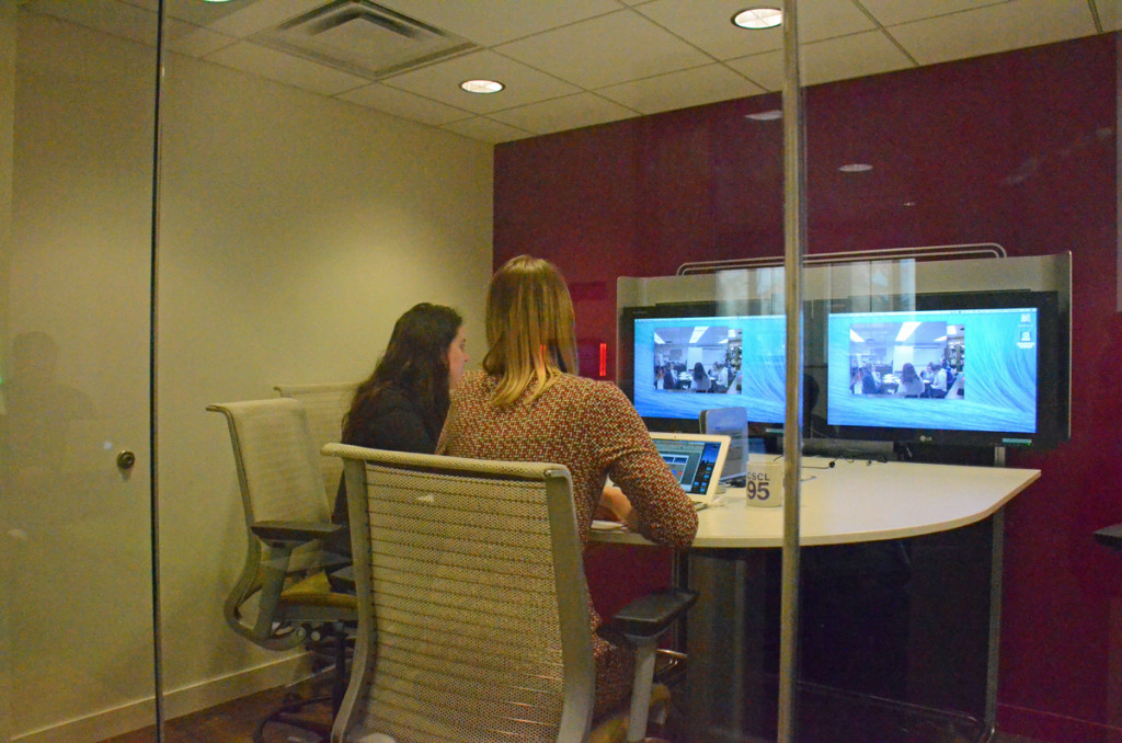 Anna Arias and Betsy Davis, instructors in the Elementary Teacher Education program, watch video of their students practicing teaching, in the Brandon Center at the University of Michigan.