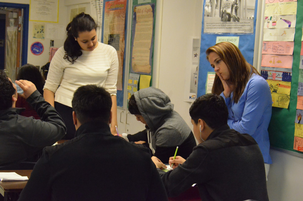 Teaching resident Grace Tesfae (left) working with students at Cesar Chavez Academy High School in Detroit. The classroom teacher, Cortney Kosmala-Jackson, is on the right.