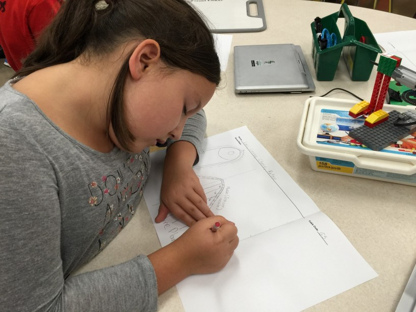 Lauren Damico, a fifth grader, draws her contribution to the design of her class's Rube Goldberg machine.