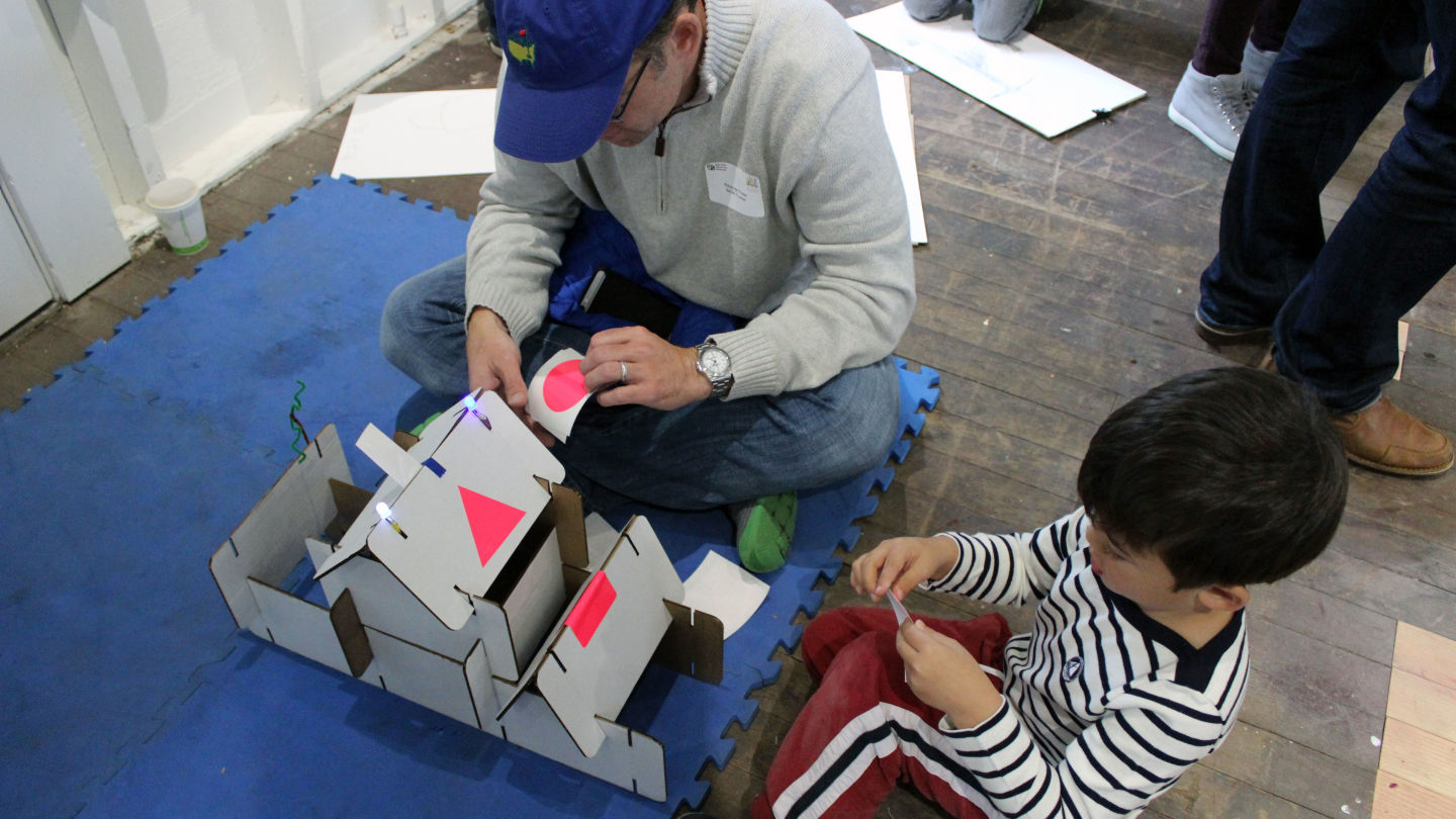 A dad and son beautify the building they built with pre-cut cardboard pieces.