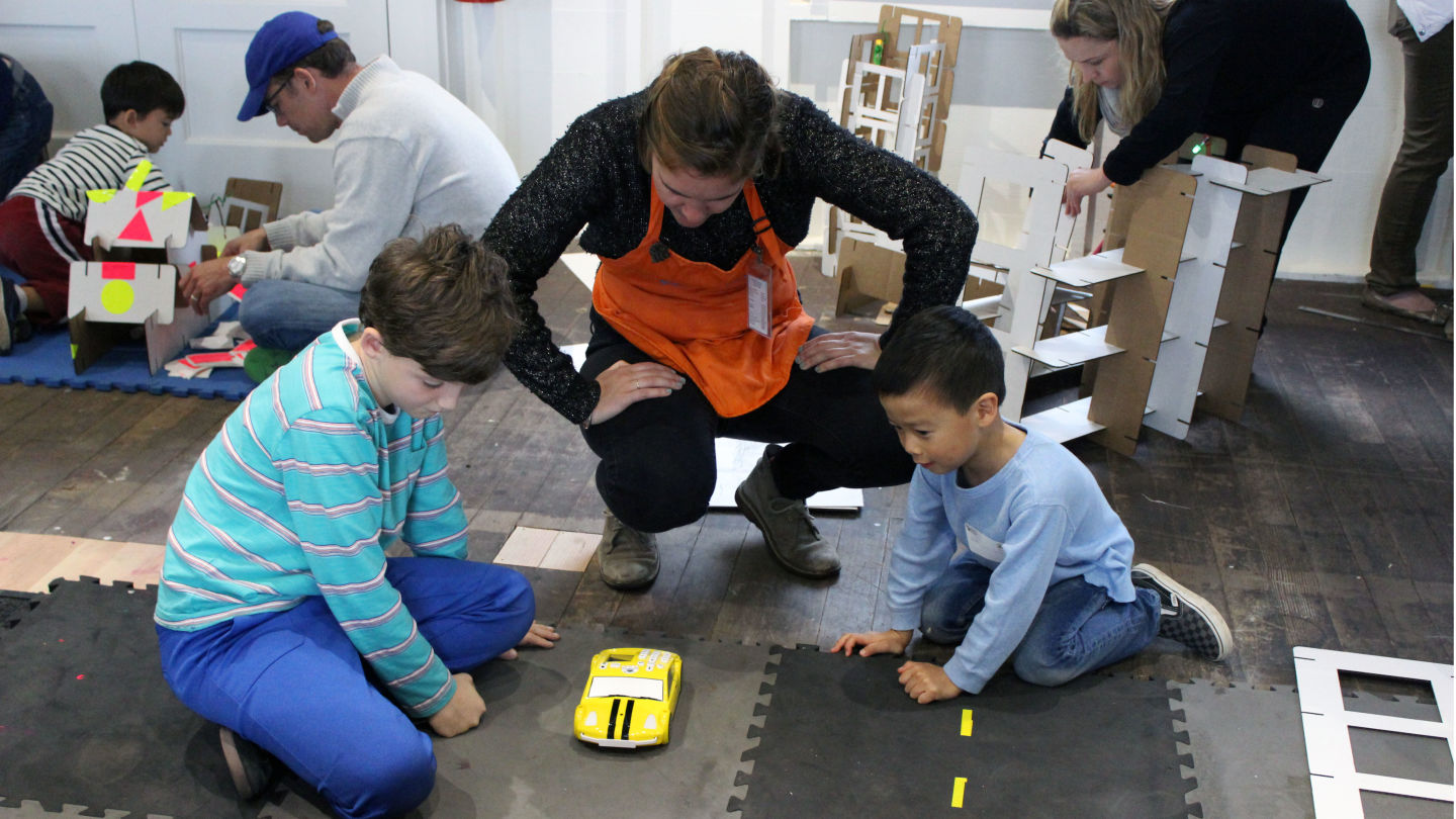 A facilitator helps kids figure out how to program one of the cars in the Fab Lab.