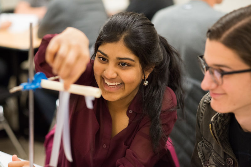 Students Geya Kairamkonda, left, and Patrick Murphy perform an experiment on elecitric charge using Scotch tape during a physics tutorial session. Their class utilizes Learning Assistants as tutors.