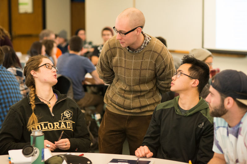 Learning Assistant Michael Byars, standing, talks with, from left, students Anna Eydinova, Aaron Higa, and Austin Reed during an evolutionary biology class.