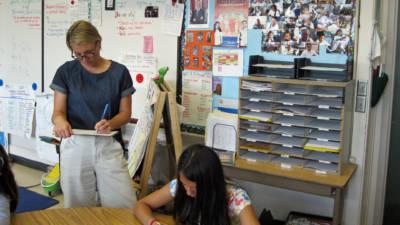 Third grade teacher Lauren Christensen observes fifth graders as they work on a problem individually.