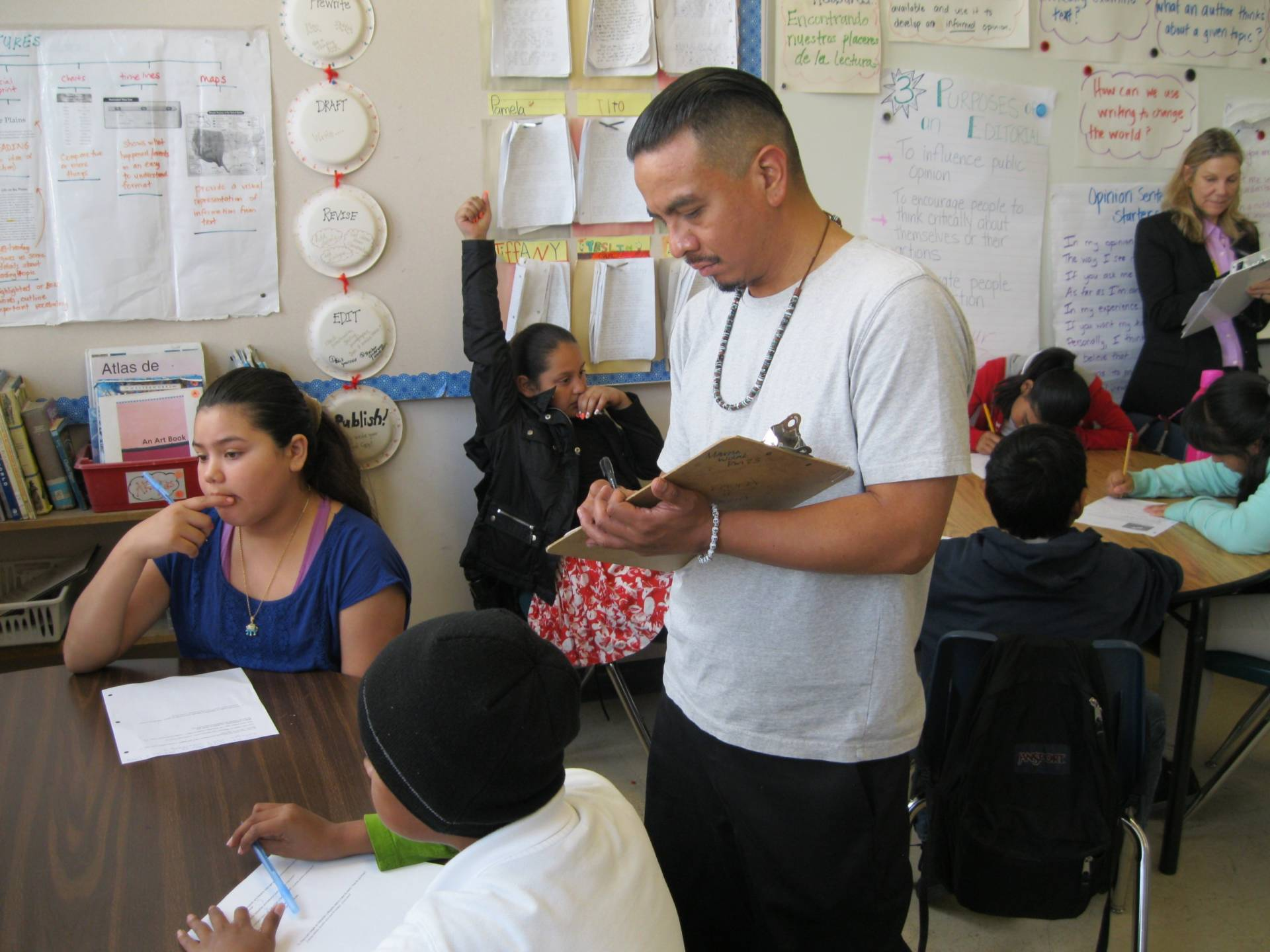 Fourth grade teacher Luis Novoa observes fifth graders working on a fractions problem.