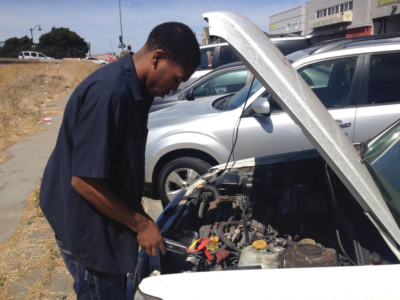 Kris examines a car at L&L Auto Shop.