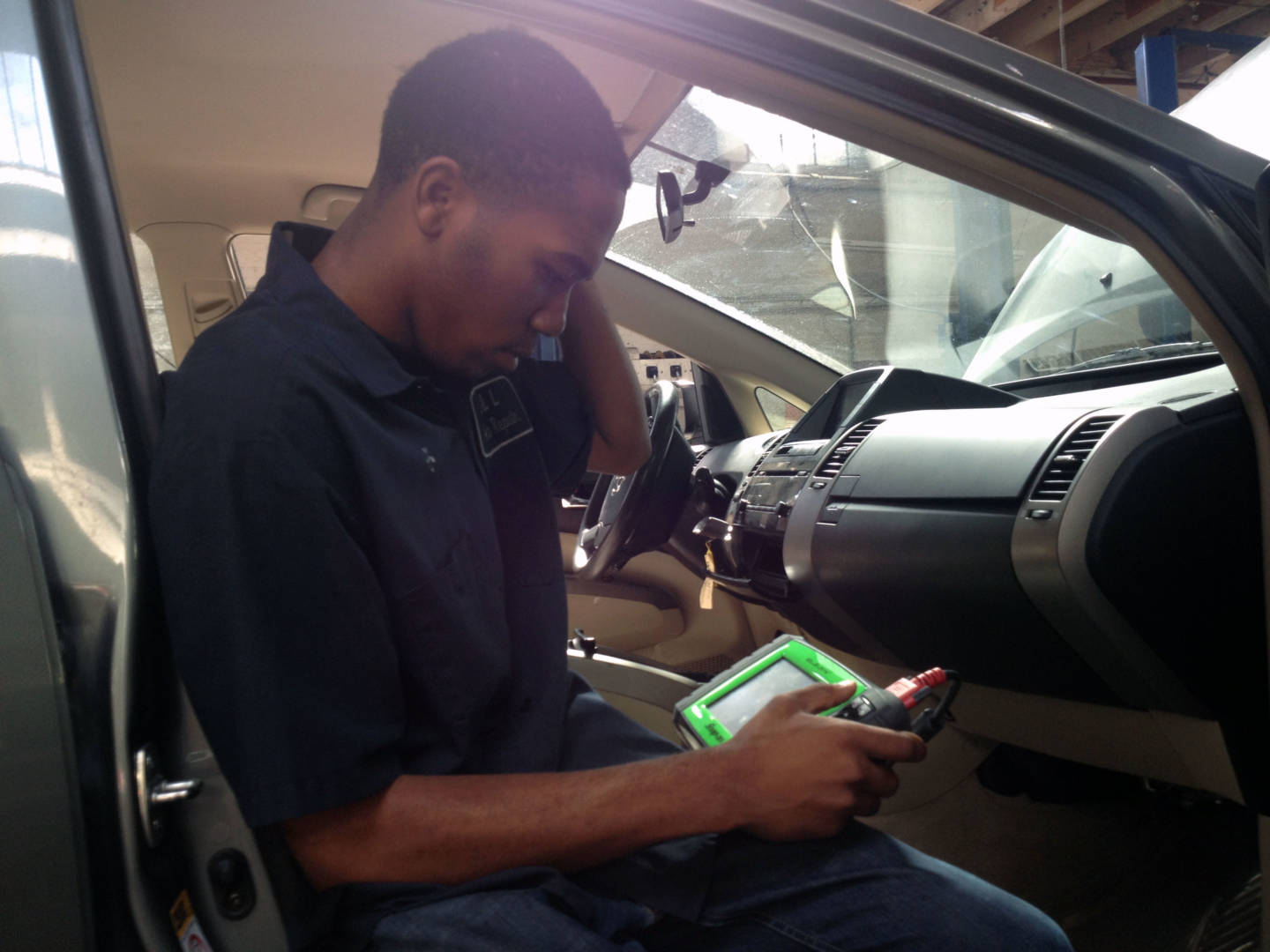 Kris uses specialized equipment to look at information on a car's computer.