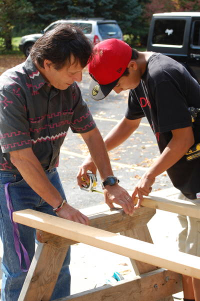 John Gizzi is helping Kirwin Parsons to build a picnic table for the school.