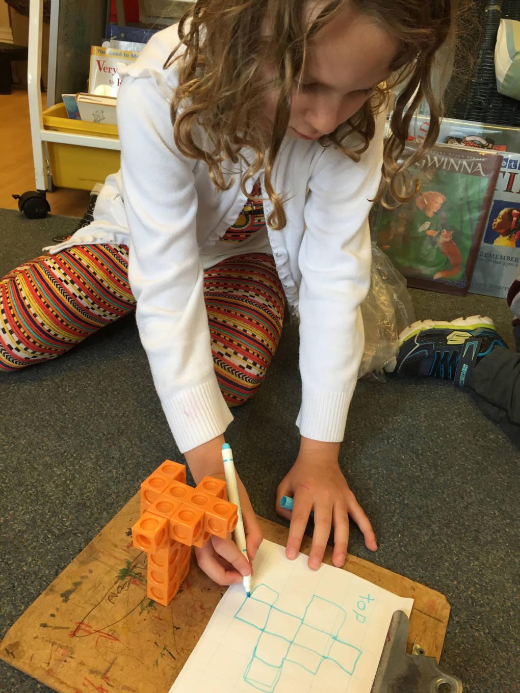 Student draws a 3D shape.