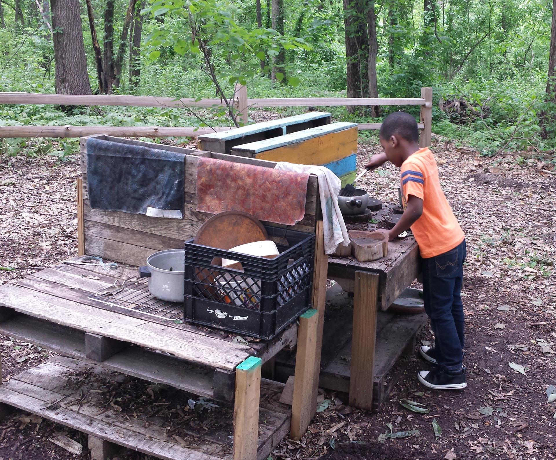 A student cooks a meal using an outdoor kitchen in the Little Creek Nature Area's Discovery Classroom.