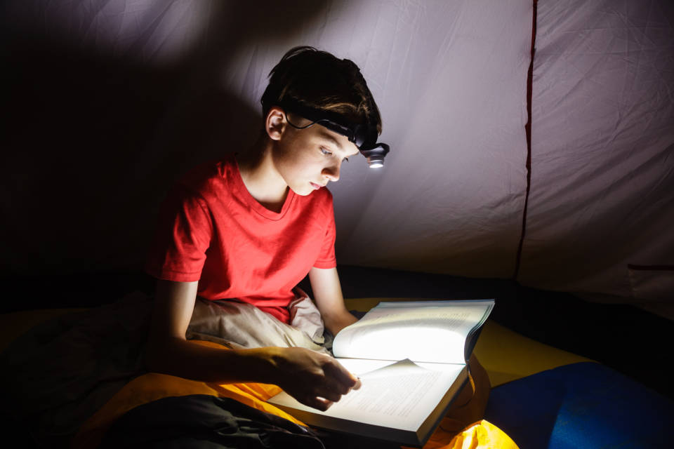Photo: Boy reading with a headlamp, ww2.kqed.org/mindshift