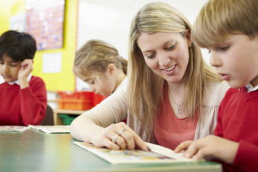Teacher Helping Male Pupil With Reading At Desk Smiling