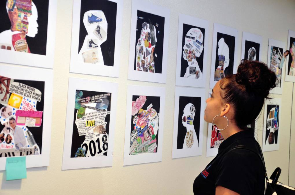 "A family member looks at the gallery of student portraits portrayed on ""graduation day"" of Summer Bridge."
